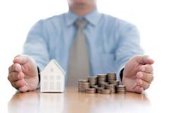 Stapel van stijgend muntstukken en huismodel met zakenman stock foto's