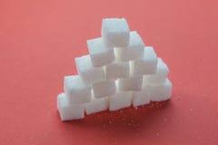 Stapel van Sugar Cubes Stacking op rode achtergrond royalty-vrije stock afbeeldingen