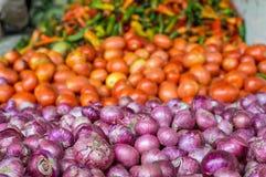 Stapel van uien naast een stapel van tomaten en peper stock foto's