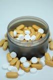 Stapel van vitaminen in zwarte fles op witte achtergrond royalty-vrije stock afbeelding