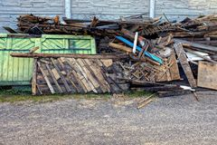 Stapel van vuilnis van oude planken in de binnenplaats in de straat stock afbeelding