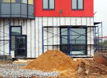 stapel van zand en steiger bij bouwwerf dichtbij het onderflatgebouw Royalty-vrije Stock Afbeelding
