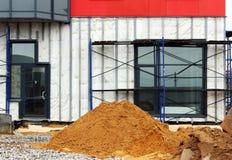 stapel van zand en steiger bij bouwwerf dichtbij het onderflatgebouw Stock Afbeeldingen
