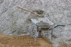 Stapel van zand met schop en kruiwagen Royalty-vrije Stock Afbeeldingen