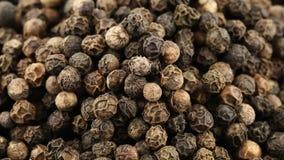 Stapel van zwarte peperbollen die dichte omhooggaande mening roteren - de zwarte peperbollen worden gebruikt als kruiden in de ke stock video
