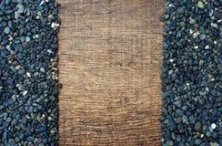 Stapel van zwarte stenen op het oude hout Stock Foto