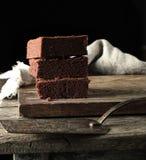 Stapel vierkante stukken van gebakken bruine browniepastei op een houten raad stock foto