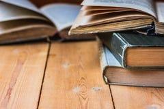 Stapel von altem geschlossenem und von offenen Büchern auf gealtertem hölzernem backgound, negativer Raum für Text Lizenzfreies Stockbild