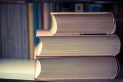 Stapel von alten Büchern auf Regal in der Bibliothek Stockbilder