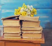 Stapel von alten Büchern mit einem Blumenstrauß von gelben Blumen lizenzfreie stockfotografie