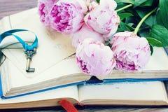 Stapel von alten Büchern mit rosa Blumen Stockfoto