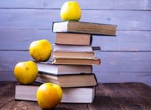 Stapel von alten Büchern und von Äpfeln auf hölzernem Hintergrund stockbild