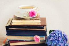 Stapel von alten Büchern und von Post mit Tasse Tee lizenzfreies stockbild