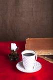 Stapel von alten Büchern, von Tasse Kaffee und von alter Kerze auf dem Rot Lizenzfreie Stockfotografie