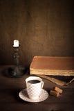 Stapel von alten Büchern, von Tasse Kaffee, von Süßigkeit und von Kerze auf dem alten w Stockfotos