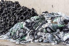Stapel von alten benutzten Reifen und zweiter Stapel von Plastiktaschen und Plastik auf der alten Wand Stockbilder