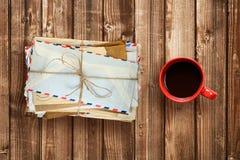 Stapel von alten Umschlägen und von Kaffeetasse auf Holztisch Lizenzfreie Stockfotografie