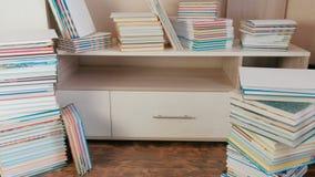 Stapel von Büchern auf dem Boden und auf dem Wandschrank stock video footage