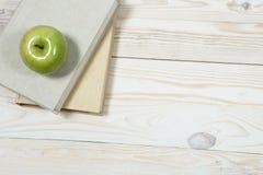Stapel von Büchern und von Apfel auf dem Tisch Stockfoto