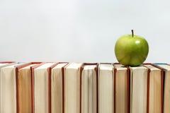 Stapel von Büchern und von Apfel auf dem Tisch Lizenzfreie Stockbilder