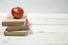 Stapel von Büchern und von Apfel auf dem Tisch Lizenzfreies Stockbild