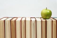 Stapel von Büchern und von Apfel auf dem Tisch Lizenzfreie Stockfotos