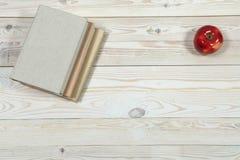 Stapel von Büchern und von Apfel auf dem Tisch Stockfotografie