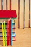 Stapel von Büchern und von farbigen Bleistiften auf einer Holzoberfläche Lizenzfreie Stockfotografie