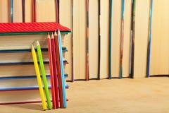 Stapel von Büchern und von farbigen Bleistiften auf einer Holzoberfläche Stockbilder