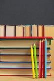 Stapel von Büchern und von farbigen Bleistiften auf einer Holzoberfläche Lizenzfreies Stockbild