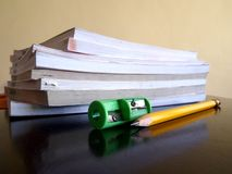 Stapel von Büchern, von Bleistift und von Bleistiftspitzer Lizenzfreies Stockfoto