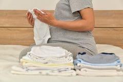 Stapel von Babykleidung und von schwangerer Frau auf einem Bett stockfotografie
