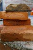 Stapel von braunen Ziegelsteinen und von Bauwerkzeug Lizenzfreies Stockbild