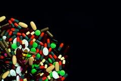 Stapel von bunten Tabletten und von Kapselpillen auf schwarzem Hintergrund Globale Gesundheitspflege Drogenkonsum in den älteren  Stockfotos