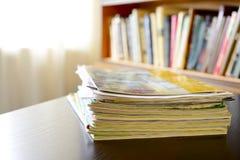 Stapel von Dateien mit einem Bücherregal im Hintergrund Stockbilder