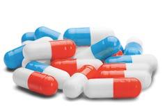 Stapel von den medizinischen Pillen blau und von roter Farbe auf weißem Ba Stockbild