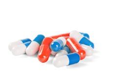 Stapel von den medizinischen Pillen blau und von roter Farbe auf weißem Ba Lizenzfreies Stockbild