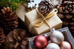 Stapel von den Weihnachts-und Neujahrsgeschenk-Kästen eingewickelt Kraftpapier-bunte Ball-große Kiefern-Kegel-in der grünen Tanne Stockfotografie