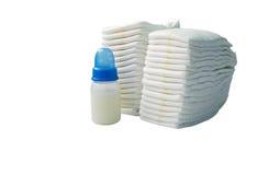 Stapel von den Windeln und von Babyflaschen lokalisiert auf weißem Hintergrund Lizenzfreie Stockfotografie