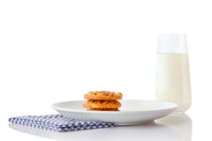 Stapel von drei selbst gemachten Erdnussbutterplätzchen auf weißer keramischer Platte auf blauer Serviette und Glas Milch Stockfotos