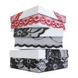 Stapel von drei stilvollen weißen Geschenkboxen, verziert mit vorzüglichem schwarzem und rotem Spitzeband Stockfotografie