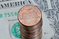 Stapel von einem US-Cent prägt auf einem Dollarschein Lizenzfreies Stockfoto