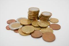 Stapel von Euromünzen von verschiedenen Bezeichnungen auf einem weißen Schreibtisch, flache Schärfentiefe stockfotos