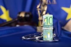 Stapel von 100 Euros umgeben durch die Handschellen auf einer Flagge von EU Stockfoto