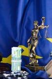 Stapel von 100 Euros umgeben durch die Handschellen auf einer Flagge von EU Stockbilder