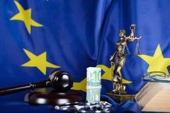 Stapel von 100 Euros umgeben durch die Handschellen auf einer Flagge von EU Stockbild