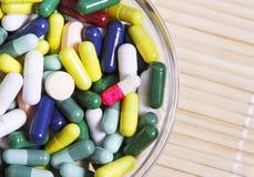 Stapel von farbigen Pillen in einer Glasschüssel Stockfotografie
