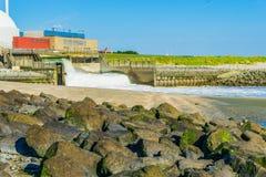 Stapel von Felsen auf der Strandbetrachtung auf einem Wasserfall und einer Industrie Stockbilder