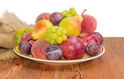 Stapel von Früchten auf dem großen Teller auf Holzoberfläche Lizenzfreies Stockfoto