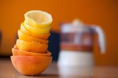 Stapel von frisch zusammengedrückten Zitrusfrüchten mit dem Juicer voll vom Saft im Hintergrund Lizenzfreies Stockbild